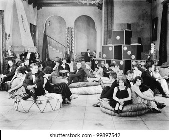 Group of people sitting on oversized cushions in a hall