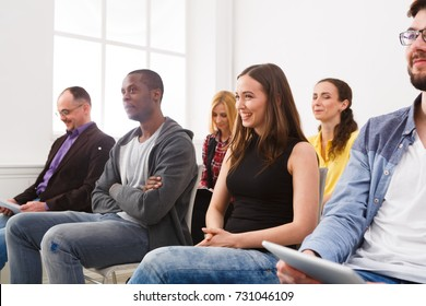 Group of people sitting at seminar, copy space. Interested and laughing audience listening to speaker. Education, conference, workshop concept