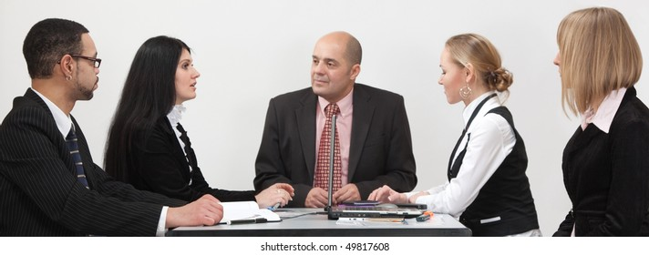 A group of people sitting symmetrically around the table at a business conference