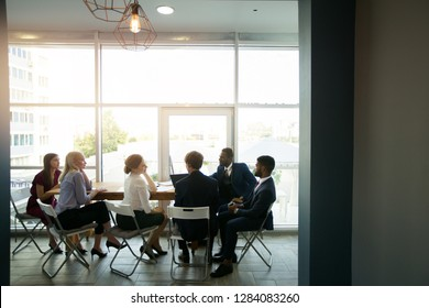 a group of people sitting at a table at work in an office at a meeting