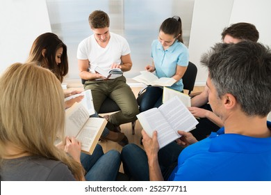 Group Of People Sitting Together Reading Books