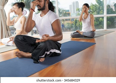 Group of people sitting in yoga position and practicing nostril breathing (nadi shodhana pranayama)
