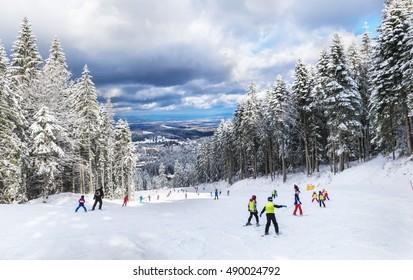 Group of people skiing on a ski slope in Poiana Brasov resort, in winter season, in Romania