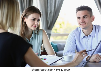 Group of people solves the problem in the course of a conversation sitting at a table in a cafe denigrate education teaching each other questions and answers training