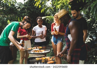 Group of people standing around barbecue grill, chatting, drinking and eating at summer outdoor party and holidays concept.