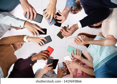Group Of People Standing In Circle Using Smartphone