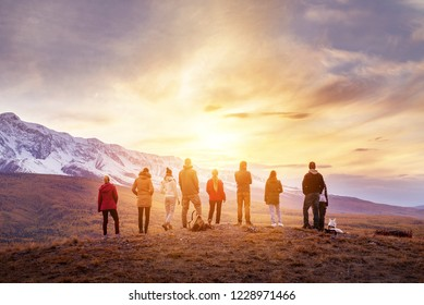 Group of people stands against mountains at sunset