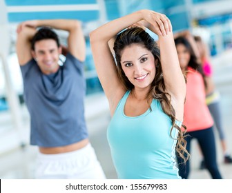 Group of people stretching at the gym and smiling