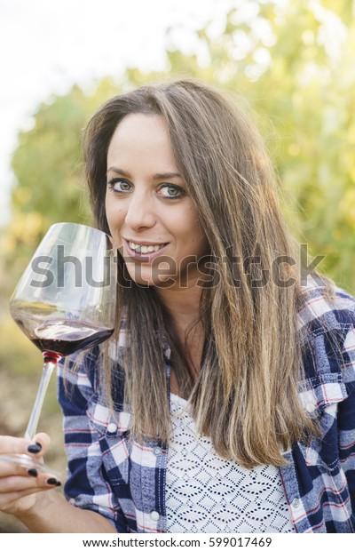 group of people tasting red wine in a vineyard