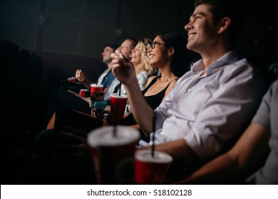 Group of people in theater with popcorn and drinks. Young friends watching movie in cinema.