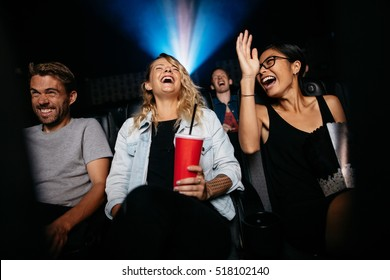 Group of people in theater with popcorn and drinks watching movie and laughing. Young women and men watching comedy movie in cinema.
