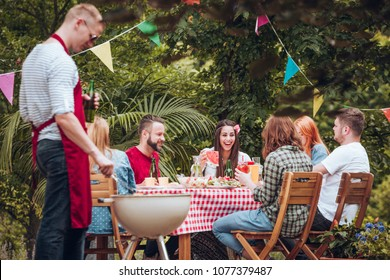 Group of people in their twenties and thirties in the garden enjoying their time together, eating and drinking, by a table