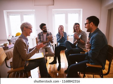 Group of people in group therapy feeling positive and motivated.