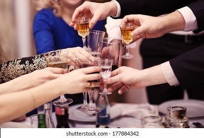 Group of people toasting at a celebration clinking their glasses together in congratulations , close up view of their hands. Film-like color correction.