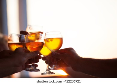 Group of people toasting each other with glasses of white wine at a celebration party, close up of their hands against a bright window with copy space