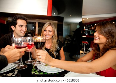 Group of people toasting looking happy at a fancy restaurant