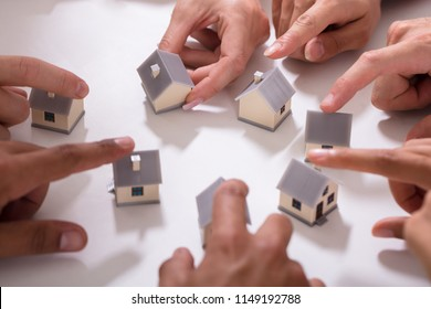 Group Of People Touching Miniature House On White Background