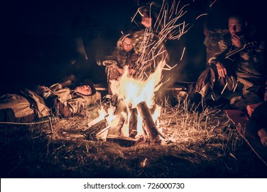 Group of people tourists relaxing by the fire in outdoors camp after long hunting day in the night