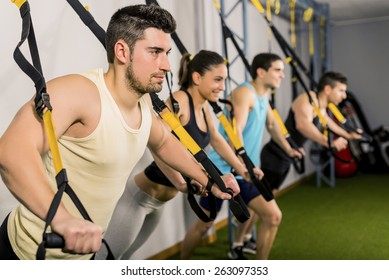 Group of people training at elastic rope in gym