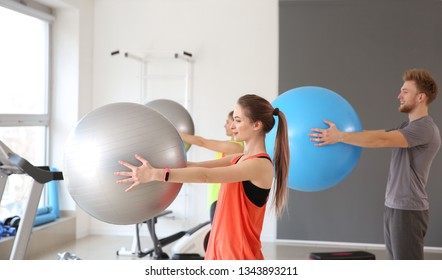 Group of people training with fitballs in gym