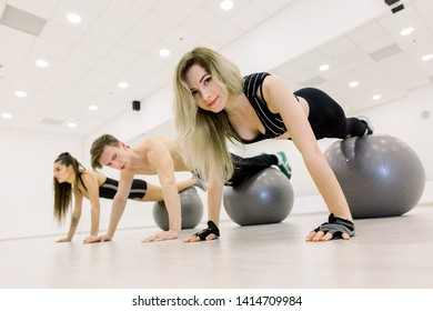 Group of people training with fitballs in gym. Two young sporty women and man doing plank with legs on fitball at gym.