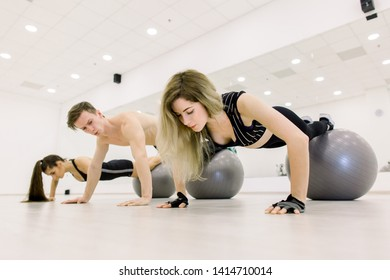 Group of people training with fitballs in gym.