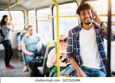 A group of people traveling by the bus with a young cheerful handsome man in the first plan of the picture who is listening to music on his headphones and smiling.