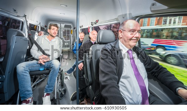 Group of people, traveling in a minivan with a disabled person in a wheel chair, surrounded by several others