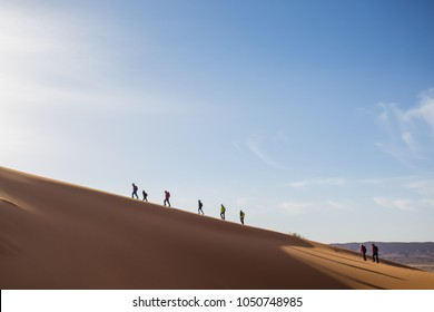 A group of people trekking on a dune to Sahara desert. Morocco.