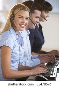 A group of people are typing on keyboards and wearing headsets.  The young woman is smiling at the camera.  Vertically framed shot.