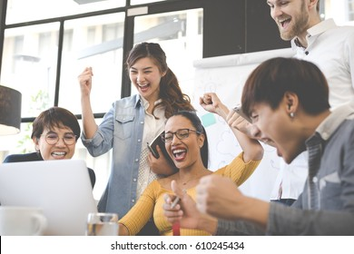 Group of people various nationality glad and cheerful for success them work with laptop at modern office. Feeling happy and enjoy with achievement project. With soft tone.