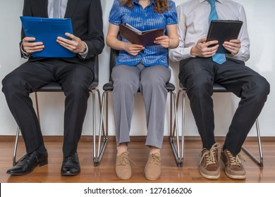 Group of people waiting for interview in a waiting room.