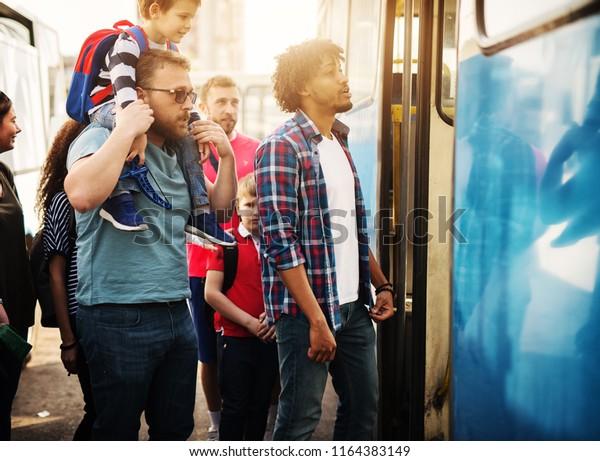 Eine Gruppe Leute wartet in der Warteschlange, um in einen Bus zu kommen.