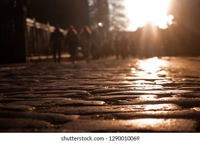A group of people walking along a cobbled street in sunset