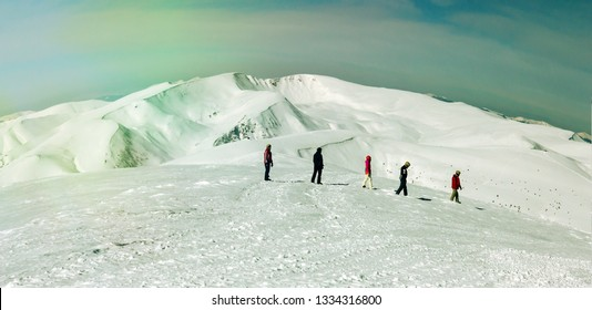 Group of people walking on fresh snow mountain terrain