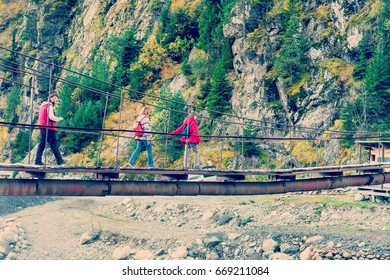 Group of people walking on a suspension bridge in the mountains