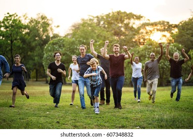 Group of people walking and running playful in the park
