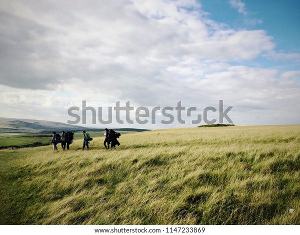 A group of people walking through grassland near the White Cliffs of Dover, England, United Kingdom.
