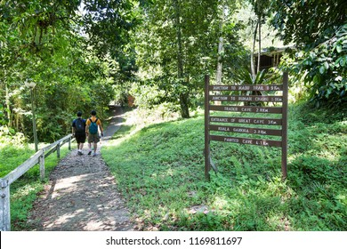 Group of people walking through tropical forest on board path trail to Niah Caves at Niah National Park, Sarawak, Malaysia.