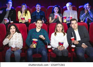 Group of people watch a horror movie at the cinema
