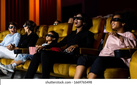 Group of people watch movie with 3D glasses in cinema theater with interest looking at the screen, exciting and enjoy