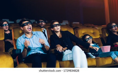Group of people watch movie with 3D glasses in cinema theater with interest looking at the screen, exciting and eating popcorn