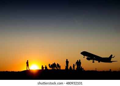 Group of people watching commercial airplane taking off during sunset on a mountain
