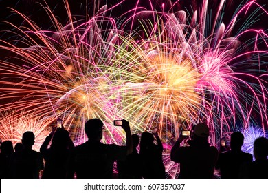 Group of people watching fireworks and using cellphones to record event