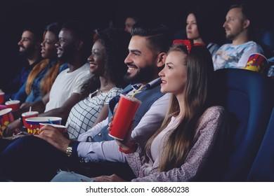Group of people watching movie in modern cinema hall.