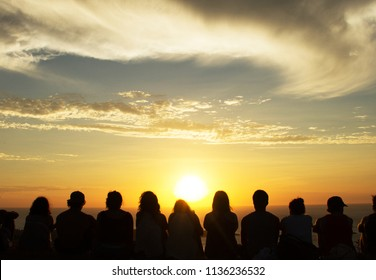 Group of people watching a sunset from a mountain