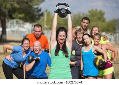 Group of people watching woman lifting kettle bell weights