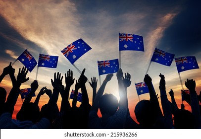 Group of People Waving Australian Flags in Back Lit