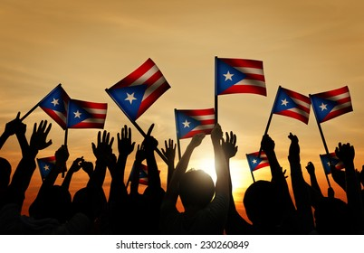 Group of People Waving Flag of Puerto Rico in Back Lit