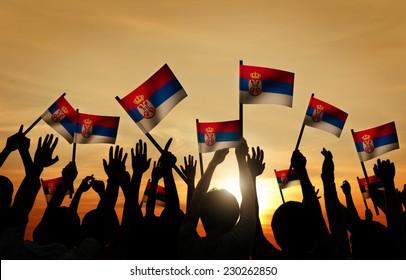 Group of People Waving Flag of Serbia in Back Lit